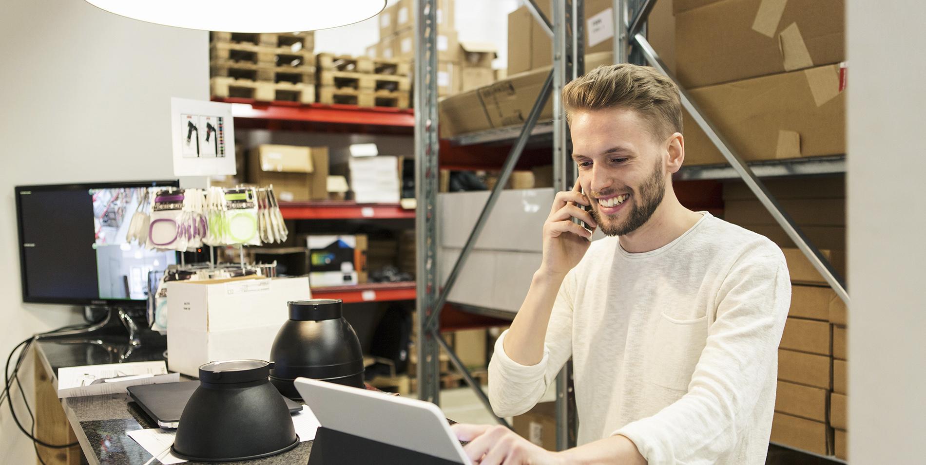 Mand arbejder ved computeren og taler i telefon på webshoppelager