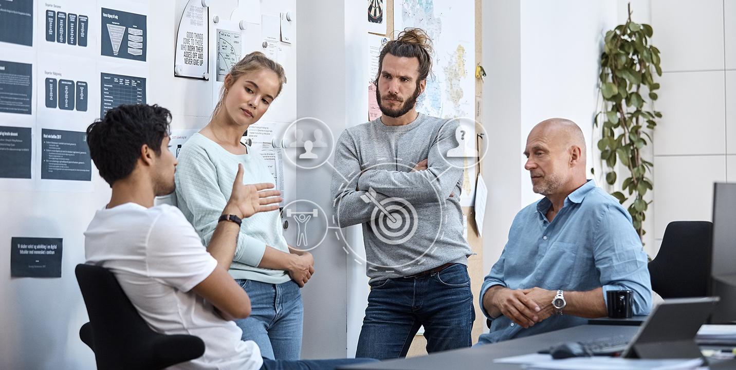 Fire forretningsfolk planlægger markedsføring på kontor