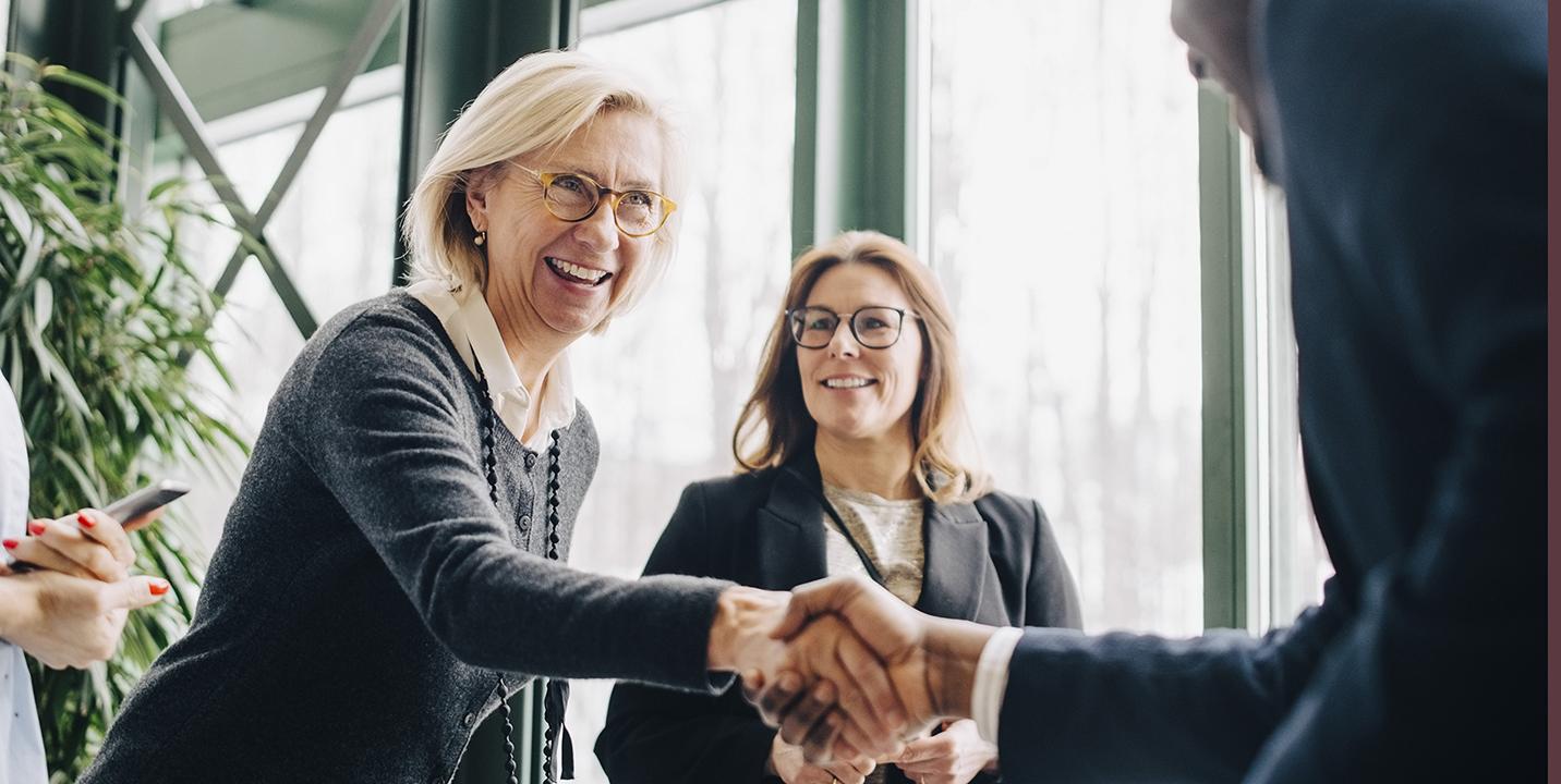 Forretningskvinder indgår en aftale og giver hånd