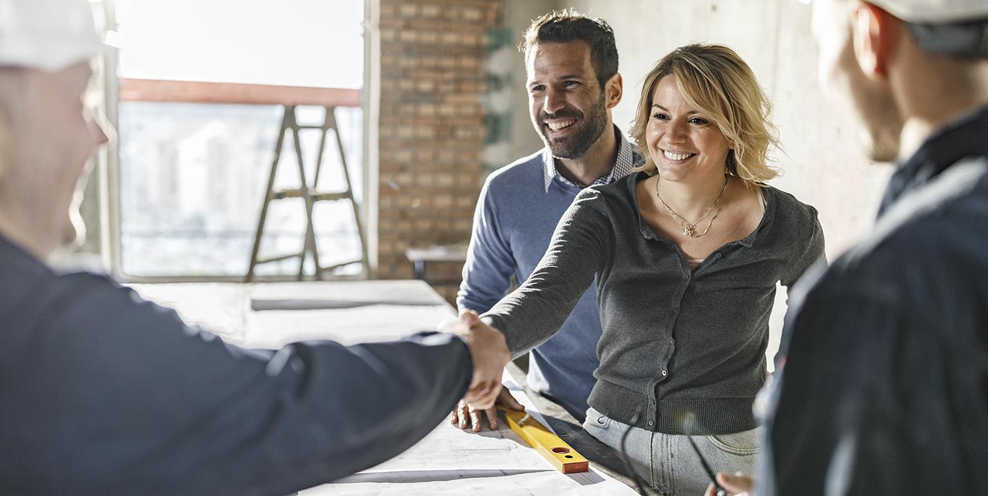 Kvinde og mand indgår en aftale og giver hånd